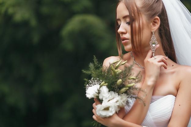 Красивая невеста в пышном свадебном платье позирует среди зелени на улице. женщина позирует в свадебном платье