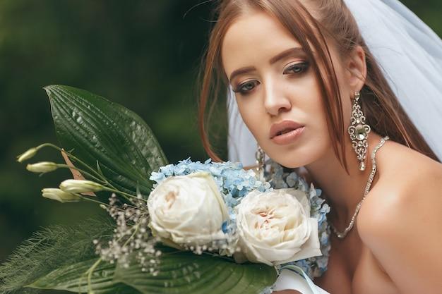 緑の中でポーズをとる壮大なウェディングドレスの美しい花嫁