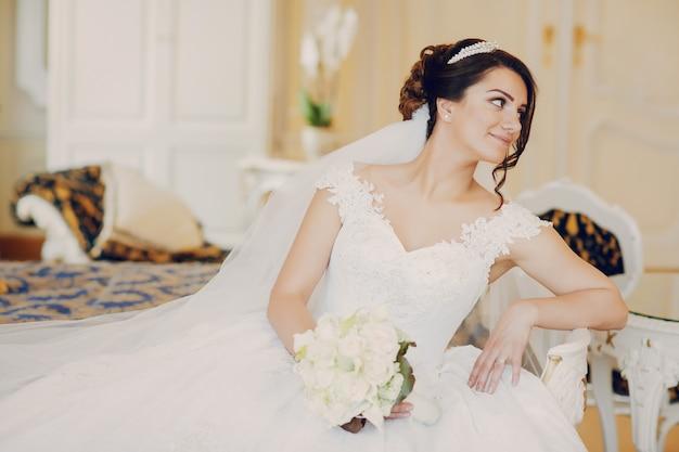 웅장한 하얀 드레스를 입고 아름다운 신부와 그의 머리에 왕관