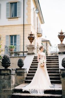 花の花束とピンクのドレスを着た美しい花嫁は、古代の別荘の階段に立っています