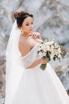 塩の山の頂上に花束を持つウェディングドレスの美しい花嫁。巻き毛の見事な若い花嫁。