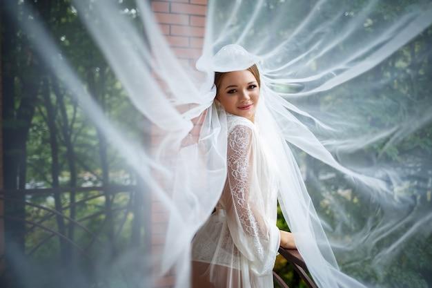 バスローブとベールで結婚式の朝の美しい花嫁