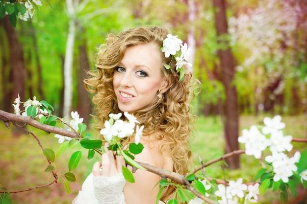 春に咲く庭園で白いドレスを着た美しい花嫁プロのメイクと髪型