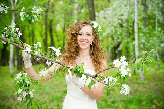 Красивая невеста в белом платье в цветущих садах весной профессиональный макияж и прическа
