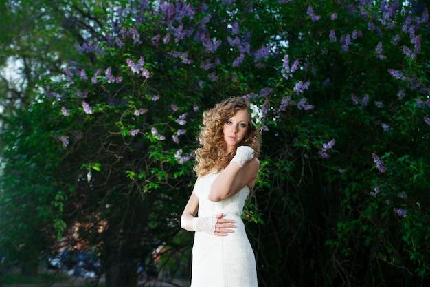 春のライラックに白いドレスを着た美しい花嫁プロのメイクと髪型