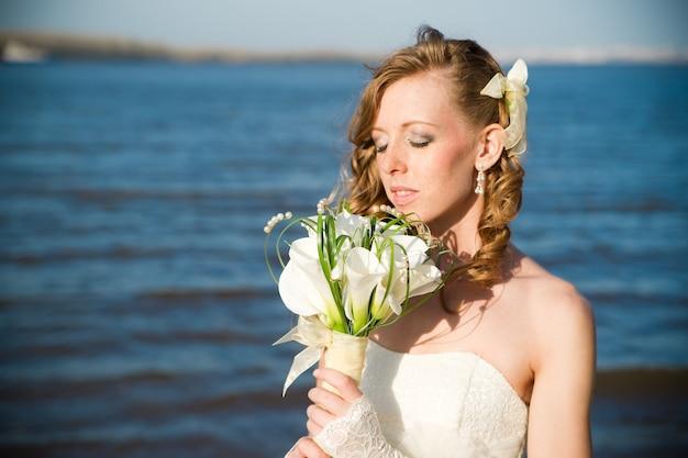 夏の川の海岸で白いドレスを着た美しい花嫁プロのメイクと髪型