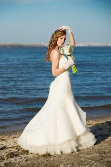 夏の川の海岸に白いドレスを着た美しい花嫁