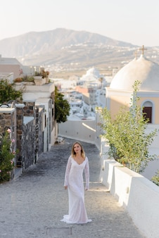 サントリーニ島のティラの街を背景にポーズをとる白いドレスを着た美しい花嫁。
