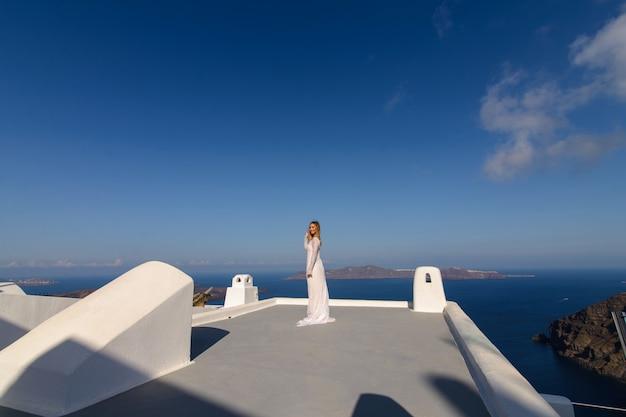 Красивая невеста в белом платье позирует на крыше дома на фоне средиземного моря в тира, санторини. Premium Фотографии