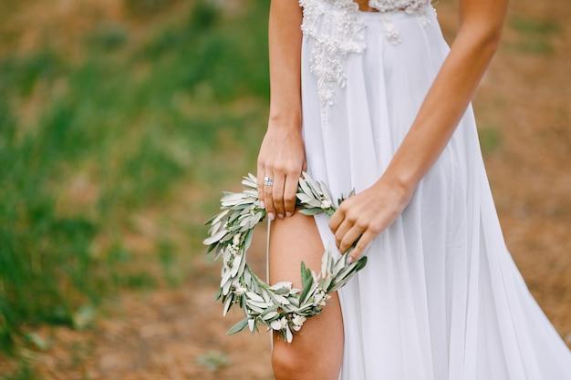 白い刺し繡のドレスを着た美しい花嫁は、オリーブの葉の花輪を保持している花嫁の足が見える