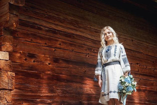 Красивая невеста в вышитой рубашке с букетом цветов на фоне деревянного дома.