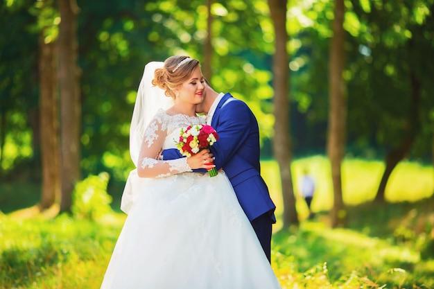 自然の中で森の中を歩いて、手を繋いでいる高価なドレスを着た美しい花嫁