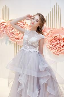 Красивая невеста в дорогом свадебном платье в присутствии крупных искусственных цветов.