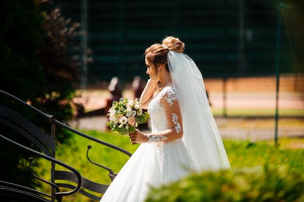 自然の背景にファッションのウェディングドレスの美しい花嫁。見事な若い花嫁は信じられないほど幸せです。結婚式の日