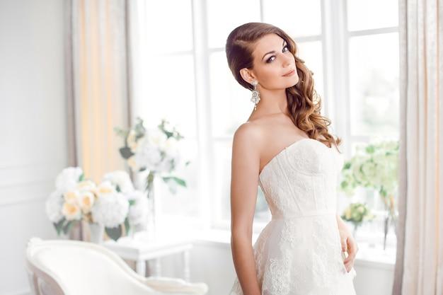 屋内でゴージャスなウェディングドレスの美しい花嫁。結婚式のファッション