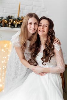 Красивая невеста в роскошном свадебном платье и красивая подружка невесты