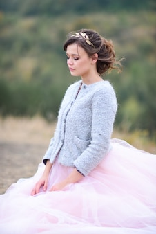 Beautiful bride in pink dress and blue jacket stands on the wind somewhere in a forest