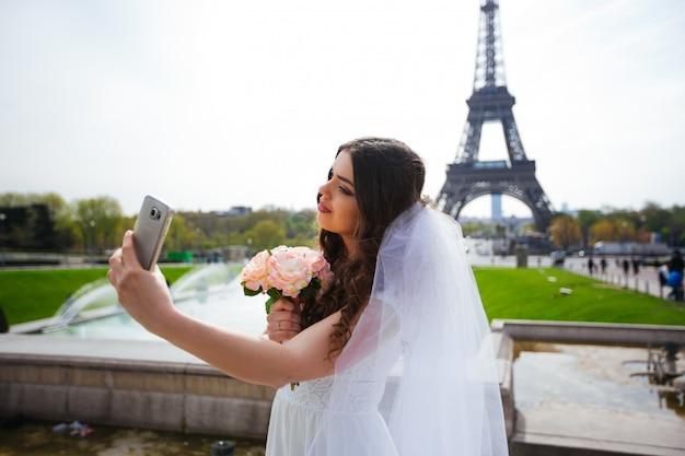豊かなウェディングドレスの美しい花嫁が広場で渦巻く