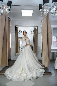 Красивая невеста в салоне позирует в свадебном платье