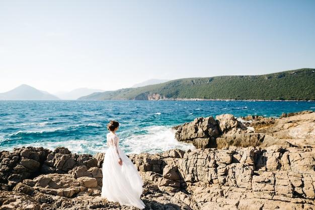 Mamula 섬의 바위 해변에 부드러운 웨딩 드레스의 아름다운 신부