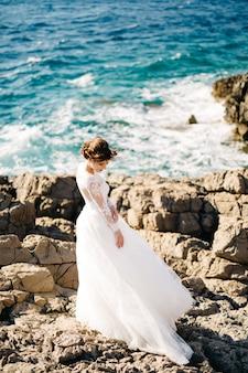 マムラ島の岩の多いビーチで優しいウェディングドレスを着た美しい花嫁。