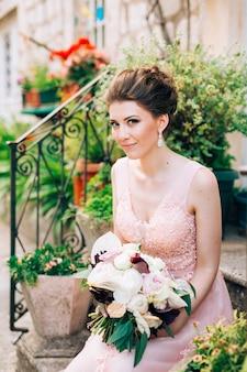 Красивая невеста в нежном свадебном платье с букетом невесты сидит на крыльце дома в перасте.