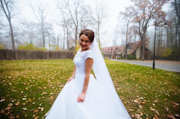 ウェディングドレスとブライダルブーケ、結婚式の花を持つ幸せな新婚女、結婚式のメイクや髪型を持つ女性の美しい花嫁。ゴージャスな若い花嫁屋外。新郎を待っている花嫁。花嫁