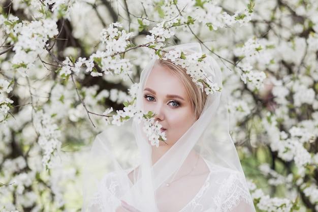 花の庭のウェディングドレスの美しい花嫁、結婚式のメイクと髪型の女性。屋外でゴージャスな若い花嫁