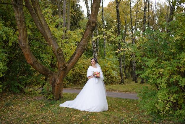 Красивая невеста в свадебном платье в парке