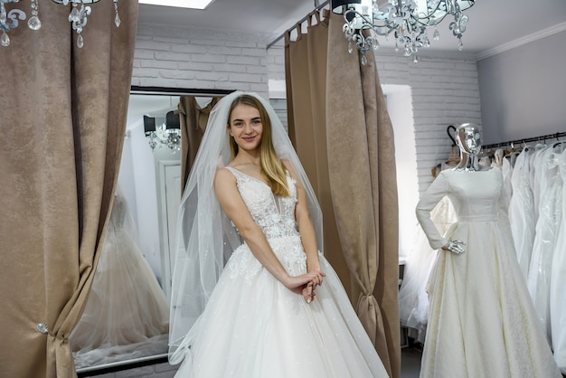 ブティックに立っているウェディングドレスの美しい花嫁