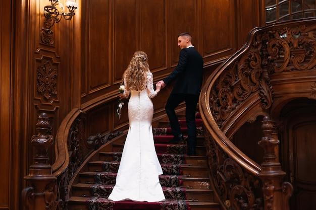 Красивая невеста в свадебном платье с красивой прической и жених в черном костюме, взявшись за руки и поднимаясь по лестнице. вид сзади.