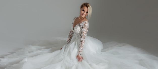 白の長い完全スカートのウェディングドレスの美しい花嫁