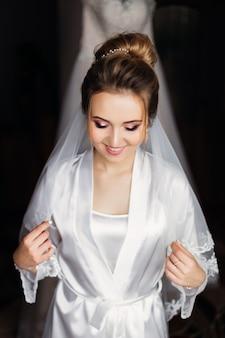 メイクとブライダルベールの白いバスローブを着た美しい花嫁は目を閉じて笑顔。