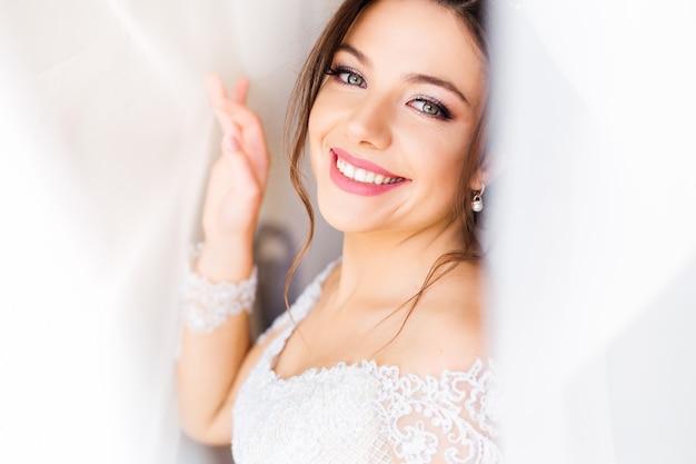 白いドレスを着た美しい花嫁がカメラを見て、カーテンの下で笑顔