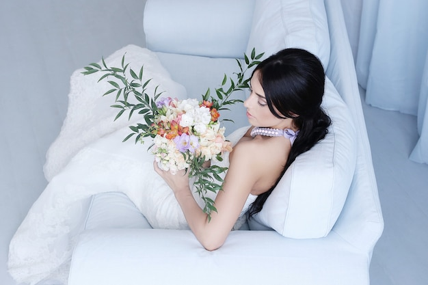 Красивая невеста в белом платье держит букет цветов