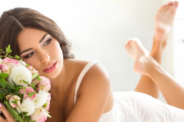 Красивая невеста в белом белье держит свадебный букет