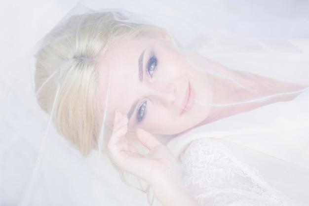 Красивая невеста в белом белье лежит на кровати, скрытой под вуалью