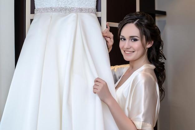 Красивая невеста в белом неглиже рядом со своим свадебным платьем улыбается