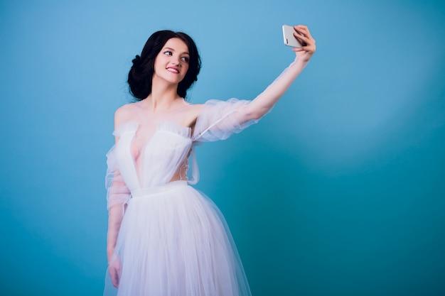 Красивая невеста в белом свадебном платье в разных позах на синей стене показывает разные эмоции
