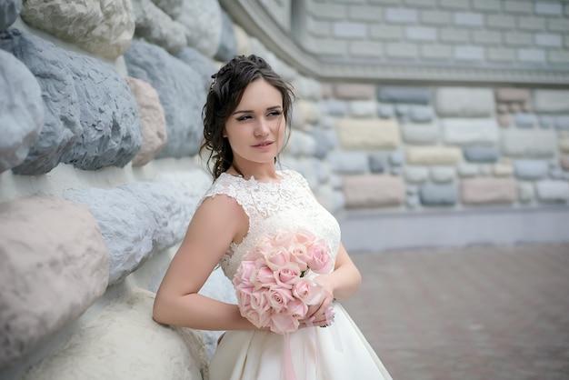 하얀 웨딩 드레스의 아름다운 신부는 돌 벽에 핑크 장미의 섬세한 꽃다발을 의미합니다.