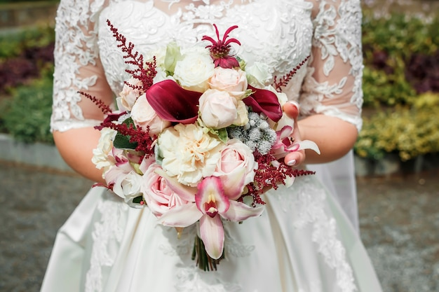 Beautiful bride is holding a wedding colorful bouquet. beauty of colored flowers