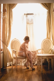 Beautiful bride in lingerie posing on chair at luxurious interior