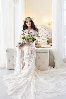 Beautiful bride in lingerie and with a wreath of flowers on her head, in the morning before the wedding. white negligee of the bride, preparing for the wedding ceremony. sexy girl on the bed
