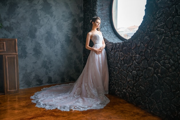 Beautiful bride in a long dress by the window