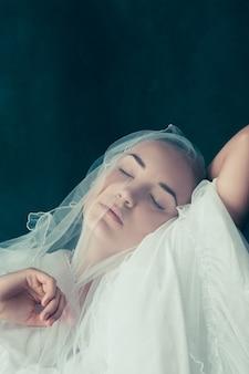 그녀가 그녀의 얼굴 앞에서 그것을 들고 그녀의 베일 너머를 바라보는 아름다운 신부
