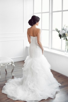 Beautiful bride looking at window. studio shot in white room from behind.