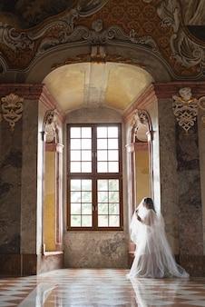 Beautiful bride in luxury baroque interior castel.