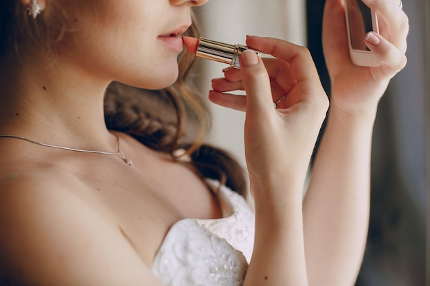 Beautiful bride painting her lips