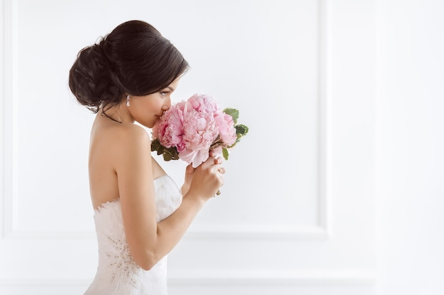 Beautiful bride perfect style. wedding hairstyle make-up luxury wedding dress and bride's bouquet