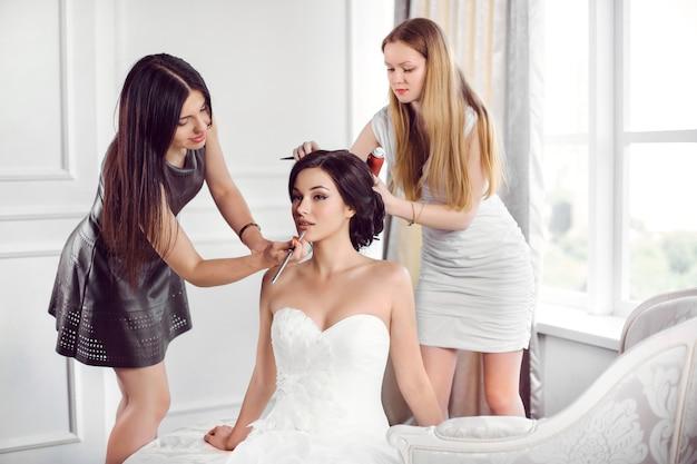 아름다운 신부 완벽한 스타일. 메이크업 아티스트에 의해 메이크업을 적용하는 흰색 드레스에 어린 소녀와